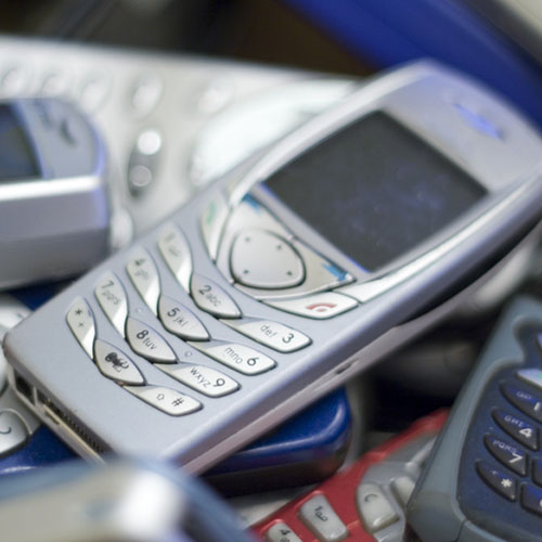 close up of silver cell phone on pile of others.
