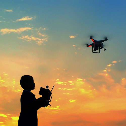 silhouette boy playing quadcopter drone in sunset