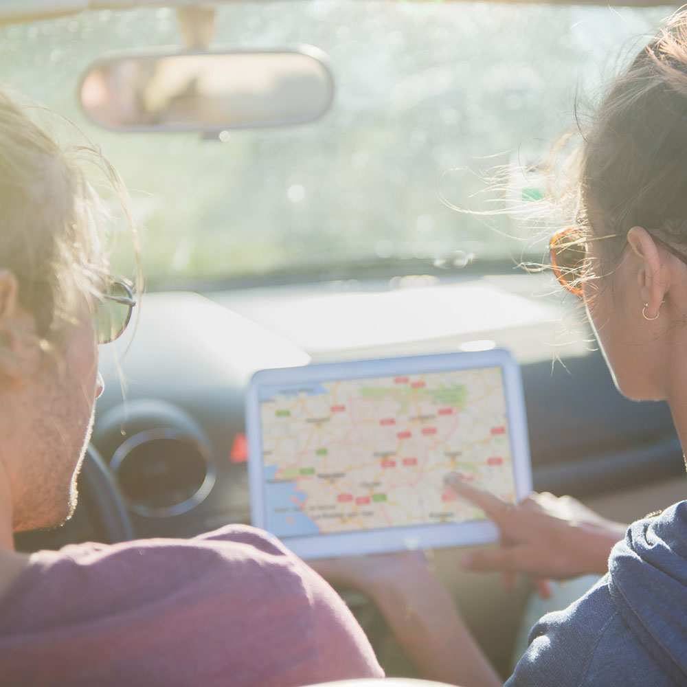 Young couple lost on a country road seeking its way on a tablet