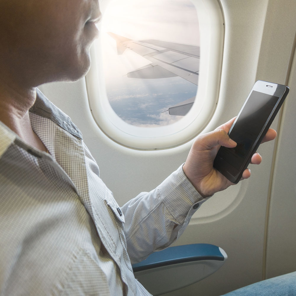 Man using smartphone in airplane.